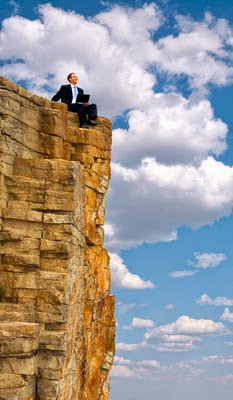 Businessman Sitting on a Rock Ledge
