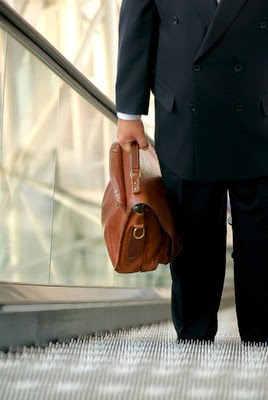 Business Leader Standing with a Bag
