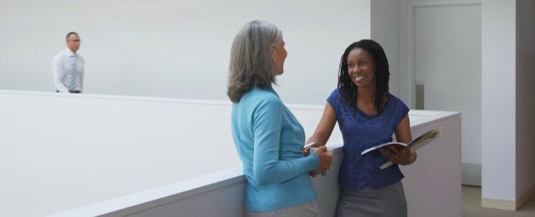 2 women talking in office hallway
